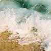 white mat black frame. A wave crashes onto a south shore beach.