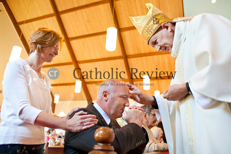 Bill Ringrose is annointed with oil by Monsignor Jeffrey N. Steenson, ordinary for the Personal Ordinariate of the Chair of Saint Peter, during a Solemn Mass for Confirmation and Reception into the Roman Catholic Church at Christ the King Church, Towson June 24. TOM McCARTHY JR. | CR STAFF