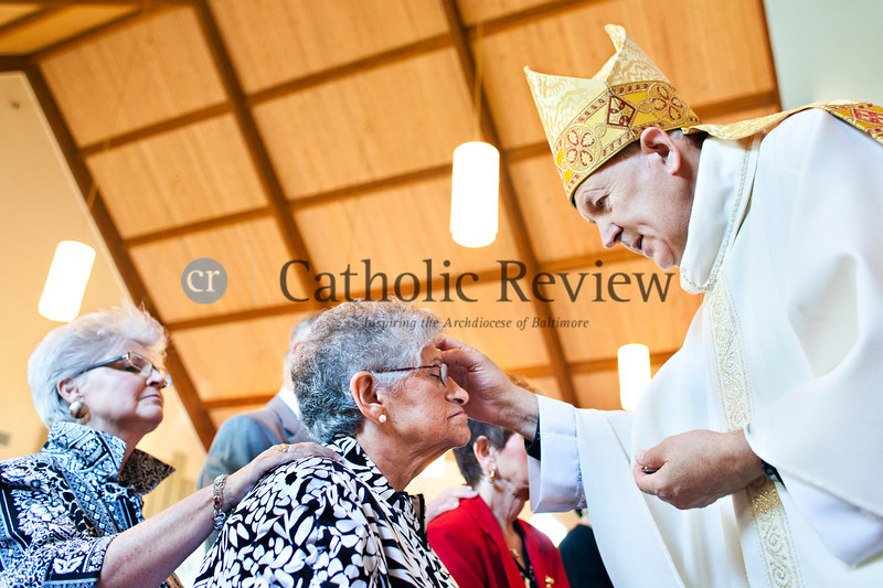 Anita Goldman is annointed with oil by Monsignor Jeffrey N. Steenson, ordinary for the Personal Ordinariate of the Chair of Saint Peter, during a Solemn Mass for Confirmation and Reception into the Roman Catholic Church at Christ the King Church, Towson June 24. TOM McCARTHY JR. | CR STAFF