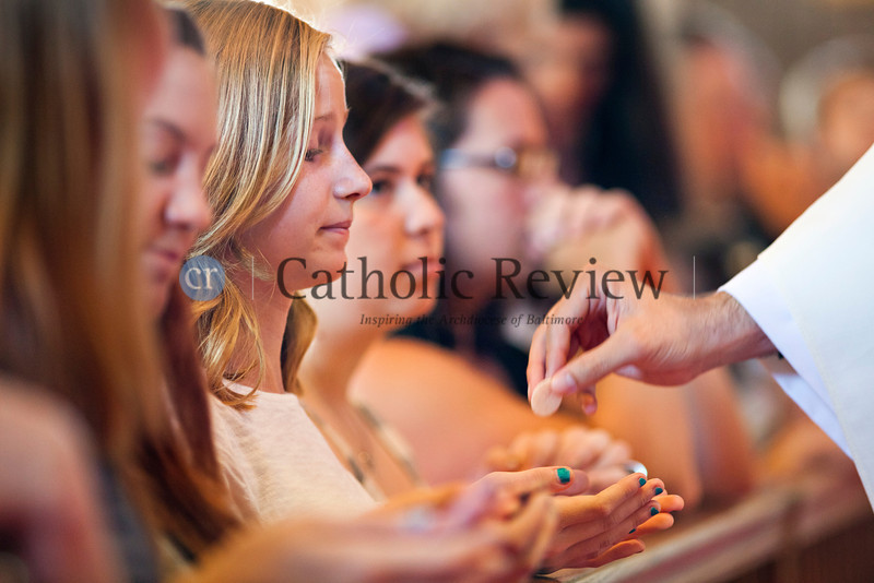 Emily Witkowski recieves communion during a Solemn Mass for Confirmation and Reception into the Roman Catholic Church at Christ the King Church, Towson June 24. TOM McCARTHY JR. | CR STAFF