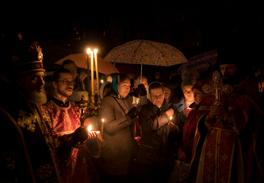 . Lithuanian Orthodox priests and worshippers hold candles and pray during an Easter vigil Mass in the Prechistensky, the Cathedral Palace in Vilnius, Lithuania, Saturday, April 15, 2017. (AP Photo/Mindaugas Kulbis)