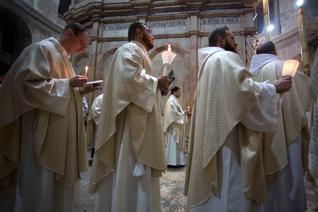 . Christian clergymen hold candles during the Easter Sunday procession at the Church of the Holy Sepulchre, traditionally believed by many Christians to be the site of the crucifixion and burial of Jesus Christ, in Jerusalem, Sunday, April 16, 2017. Millions of Christians around the world are celebrating Easter commemorating the day when according to Christian tradition Jesus was resurrected in Jerusalem. (AP Photo/Sebastian Scheiner)