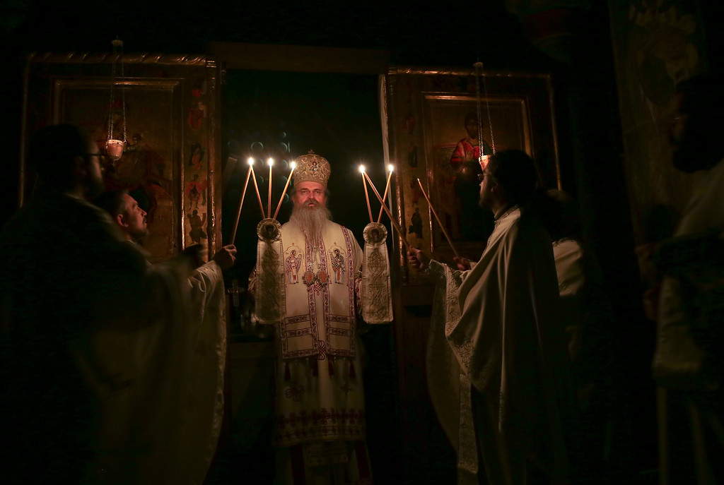 . Bishop Teodosije holds candles during an Easter vigil mass in the monastery of Gracanica during an Easter service, Kosovo Sunday, April 16, 2017. Across the world, Orthodox Christians are celebrating Easter, commemorating the day followers believe that Jesus was resurrected more than 2,000 years ago. (AP Photo/Visar Kryeziu)