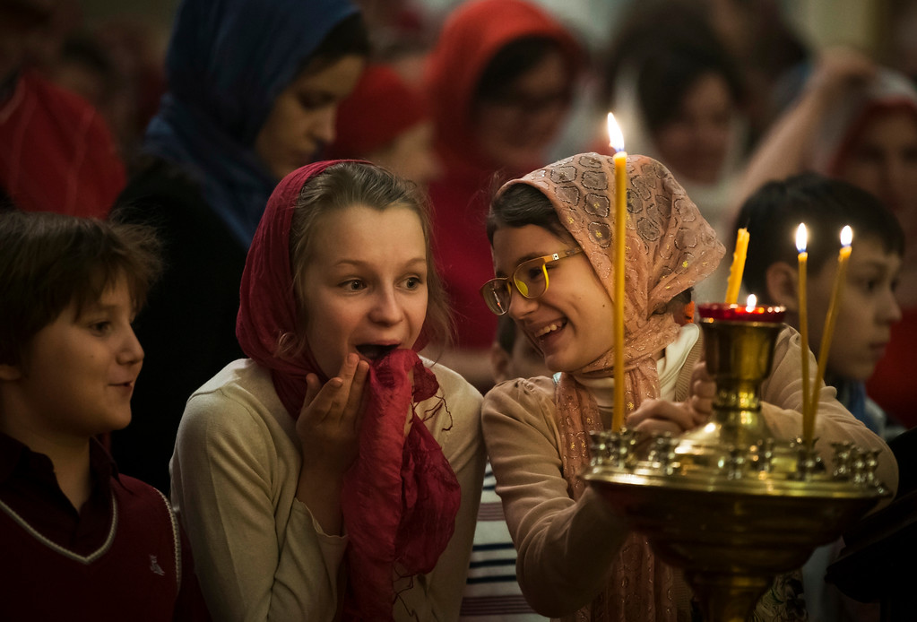 . Girls react during the Orthodox Easter service at the Church of the Holy Martyr Tatiana just next to the Kremlin Wall in Moscow, Russia, Sunday, April 16, 2017. (AP Photo/Alexander Zemlianichenko)