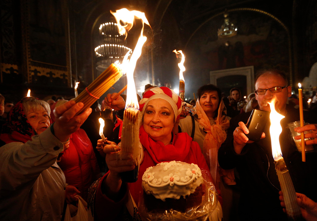. Ukrainian Orthodox faithful light candles from the Holy Fire brought from Jerusalem in St. Volodymyr Cathedral during the ceremony of the Holy Fire in Kiev, Ukraine, Saturday, April 15, 2017. The Holy Fire ceremony is part of Orthodox Easter rituals and the flame symbolizes the resurrection of Christ in a ceremony dating back to the 12th century. (AP Photo/Sergei Chuzavkov)
