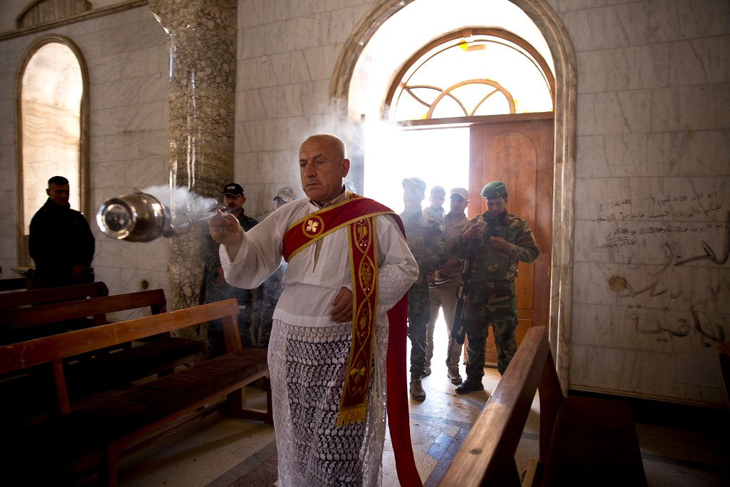 . Christian militiamen stand guard during Easter mass in Qaraqosh, outside Mosul, Iraq, Sunday, April 16 2017. The town has been gutted by Islamic State militants. Now under government control, residents have not returned. (AP Photo/Maya Alleruzzo)
