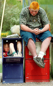 Gina O'Leary, 6, hangs out in a newspaper box as she and her bother Rober, 13, wait for their mother to pick them up in front of AVH Monday afternoon May 20, 2002.