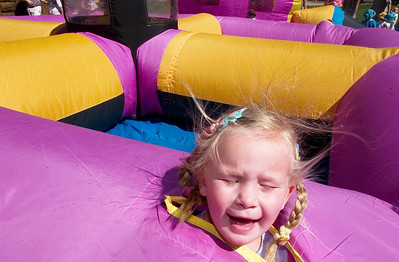 Paul Conrad/The Aspen Times With air blowing around her face, Olivia Zweig, 3, of Ashcroft pokes her head through an opening of a bouncy castle in Paepcke Park at the end of the annual Aspen Children's Parade Thursday morning May 18, 2006. Hundreds of pre-school age children, along with parents and teachers, marched from the intersection of Galena Street and Cooper Avenue to Paepcke Park.