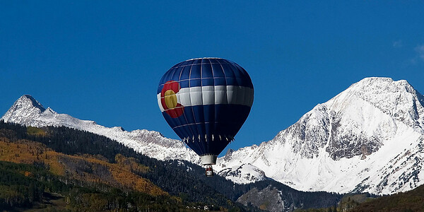 """Paul Conrad/Aspen Times Weekly With fresh snow on Capitol Peak, left, and Mount Daly, Patrick Carter of Pueblo pilots his trademark """"Colorado High"""" hot air balloon over Snowmass Village Sunday morning during the 31st annual Snowmass Balloon Festival."""
