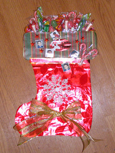 """For Rachel's preschool class, each kid had to work with their family to create a stocking for one of the other kids in the class. This is the stocking Rachel and Mommy made together. Mommy helped cut out the paper to make the stocking and tied the bow. Rachel decided where the bow should go, add the ribbon between the cuff and foot, added photos of her friend and put the snowflake ornament on. Then she and mommy """"stuffed"""" the stocking by taping all kinds of candy to the back of the stocking."""
