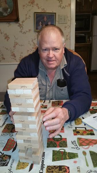 Dad playing Jenga with Sarah, plots his winning strategy.