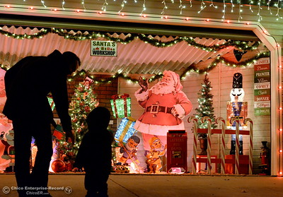 2-year-old Weston Powell takes a close look with his Dad Bill Powell at one of two homes with notable Christmas Light displays sitting side by side along Ceanothus Ave. with garages turned into religious and Santa based displays in Chico, Calif. Tues. Dec. 6, 2016. (Bill Husa -- Enterprise-Record)