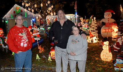 Ron Pritchard at left smiles beside neighbors Matt and Liz Gomes in front of their shared front lawn Christmas Light displays on Whitewood Way in Chico, Calif. Tues. Dec. 6, 2016. Pritchard said they had been doing the displays for about 10-years side by side. (Bill Husa -- Enterprise-Record)