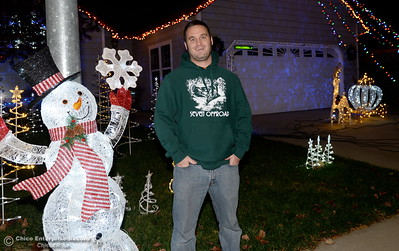 Jason Childs smiles beside his Christmas Light snowman and outline of a Cinderella-ish coach drawn by a prancing deer found at his home on Marci Way in Chico, Calif. Tues. Dec. 6, 2016. (Bill Husa -- Enterprise-Record)