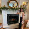 Stephanie Sallah-Tashjy stands in front of her fireplace and beautiful mantle of silver and gold decorations with mixed greenery.