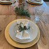 A place setting of cream and gold with napkins and greenery attached