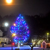 A almost full Moon (past one day), comes up over a  lit Holiday Tree on Chelmsfor Center Common. SUN/ David H. Brow