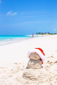 Sandy snowman with red Santa Hat on white Caribbean beach