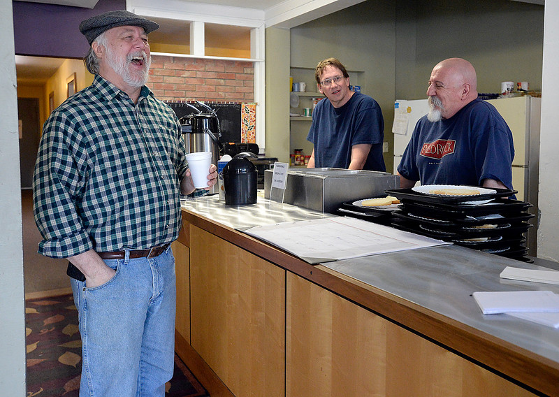 Volunteers Les Schlect, left, Brian Farrugia, right, and Carl Simmons, center, share a laugh in between serving meals to the homeless Tuesday, March 20, 2018, at Christ's Church of the Rockies in downtown Loveland. Front Porch Ministry, a ministry of Christ's Church of the Rockies, feeds homeless people a hot lunch five days a week. The church moving out of the space at the end of March and the pastor looking for a long-term temporary location downtown to continue the feeding program. (Photo by Jenny Sparks/Loveland Reporter-Herald)