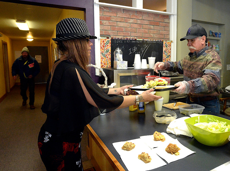 Volunteer Jerry Chacon, right, hands lunch to Yvonne Hernandez Tuesday, March 20, 2018, at Christ's Church of the Rockies in downtown Loveland. Front Porch Ministry, a ministry of Christ's Church of the Rockies, feeds homeless people a hot lunch five days a week. The church moving out of the space at the end of March and the pastor looking for a long-term temporary location downtown to continue the feeding program. (Photo by Jenny Sparks/Loveland Reporter-Herald)