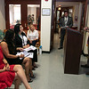 Christy Mylott, in red, listens to State Rep Michael Kushmerek at her ceremony at the Fitchburg Housing Authority's offices on Day Street where she was honored as  the Commonwealth Heroine Class of 2021. SENTINEL & ENTERPRISE/JOHN LOVE