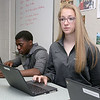 Fitchburg High School Freshman Erin Donelan talks about the chromebook that she uses in her classes. Behind her looking over his chromebook is Freshman Neville Yangsis. SENTIENL & ENTERPRISE/JOHN LOVE