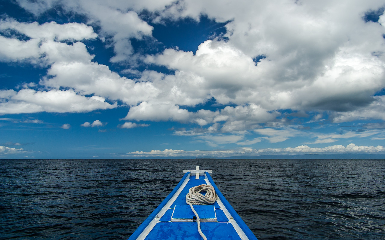 To Infinity and beyond. A bangka heads towards a dive site at Balicasag island. The sun shines through for a short while and the boat blends in with the sky, clouds and ocean. The cross at the bow is a reminiscence of the catholic heritage of the country. Fifteen minutes to the destination, and everything feels so serene.