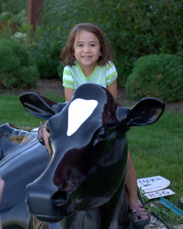 Annie sitting on a cow at Fair Oaks farm.