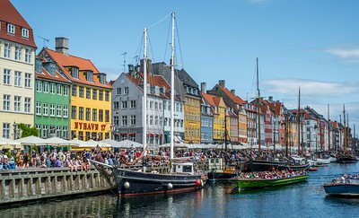 Nyhavn, the famous 17th century waterfront district features brightly colored  townhouses, restaurants, cafés and a canal packed with old wooden ships.