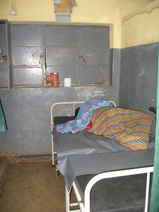 Patient in a lonely bed. There is not much to help them. There are few supplies; probably not even a Tylenol. Many go to the hospital to die.