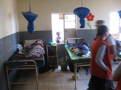 The Malawian in the window is visiting a family member. She will sleep on the ground outside and cook for the patient.