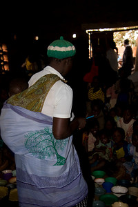 A Malawian mother at Chimbeevee Village assists with porridge preparation and distribution to hungry chldren.