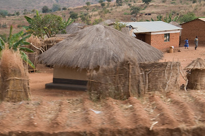 Two typical residences; first a mud house with a thatched roof and second, a brick house with a tin roof. Most bricks are made on site from the earth off their land.