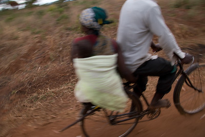 Baby on her back, this woman catches are ride on the back of a bicycle.