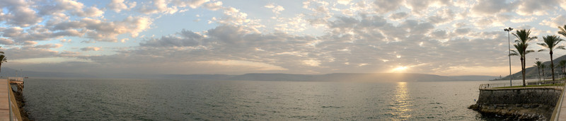 Panorama of a sunrise over the Sea of Galilee near the jetty.