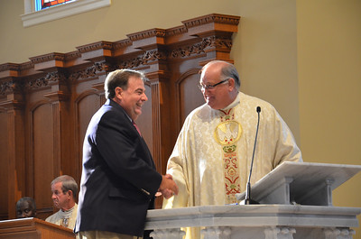 Father Paul Flood, pastor, shakes the hand of Angelo Sampona, building committee chair, during the Sept. 15 anniversary Mass.  (Photos by Cindy Connell Palmer/Archdiocese of Atlanta)
