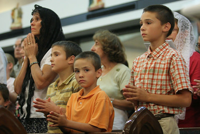 Kim Welch, wearing the black veil, and her sons (l-r) A.J., Jeremy, and Travis stand for the closing prayer.