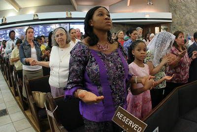 Tina Aniekwe joins the rest of the congregation in praying the Our Father.