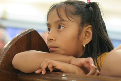 Kneeling in her pew, eight-year-old Odalis Altamirano looks toward the altar during the Liturgy of the Eucharist.