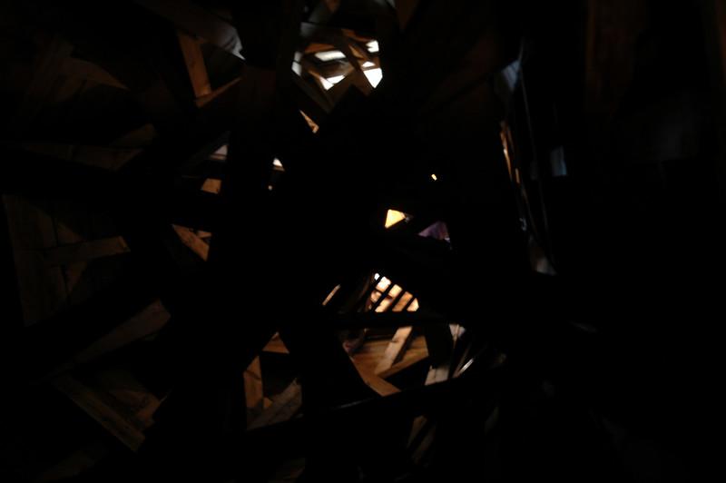 Halverwege de toren een foto omhoog. Er is wat licht dat door een paar openstaande luikjes valt.