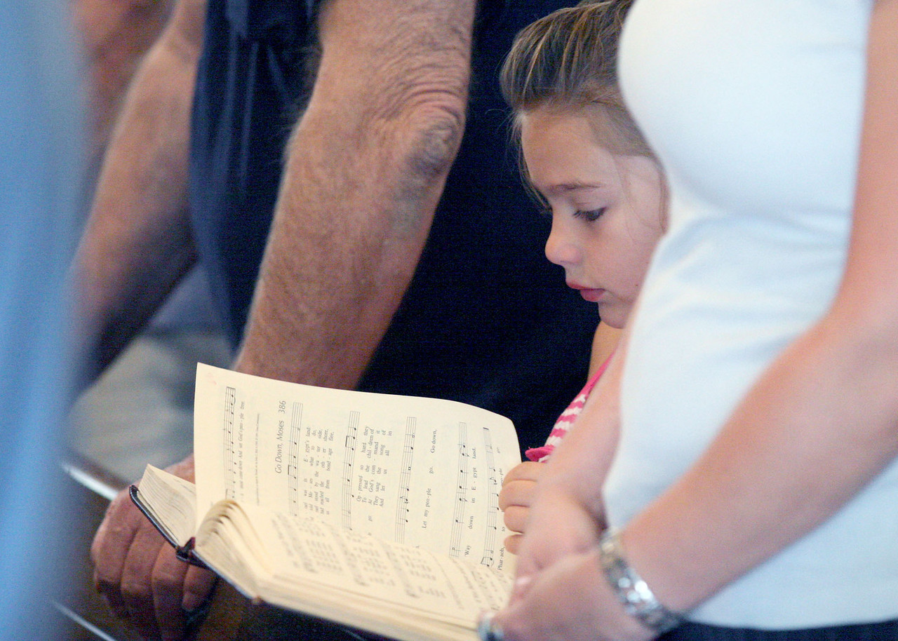 E.L. Hubbard photography<br /> A young girl follows along with the song book.<br /> Holy Trinity 150th