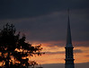 Trinity Church steeple and fir tree at dusk against colorful moody clouds - Quakertown, PA
