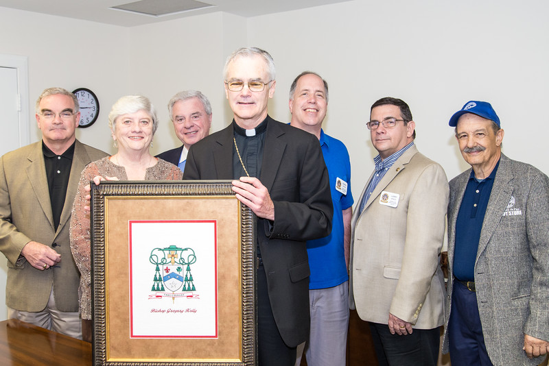 Serrans representing the four Serra Clubs of District 46E (Diocese of Dallas) present an embroidered reproduction of his coat of arms to Dallas Auxiliary Bishop Greg Kelly in honor of his recent episcopal ordination and installation. Left to right: Robert Minshall, Serra Club of Dallas; Jo-Ann Bresowar, Serra Club of the University of Dallas; Lawrence Whaley, Serra Club of Metropolitan Dallas; Bishop Kelly; Dennis Epping and Larry Montz , Serra Club of North Central Dallas; John Vallala, Serra Club of Metropolitan Dallas.