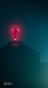 Night image of a neon cross above the dome of the Faith Family church in Sioux Falls, South Dakota. Enjoy and hold hands.
