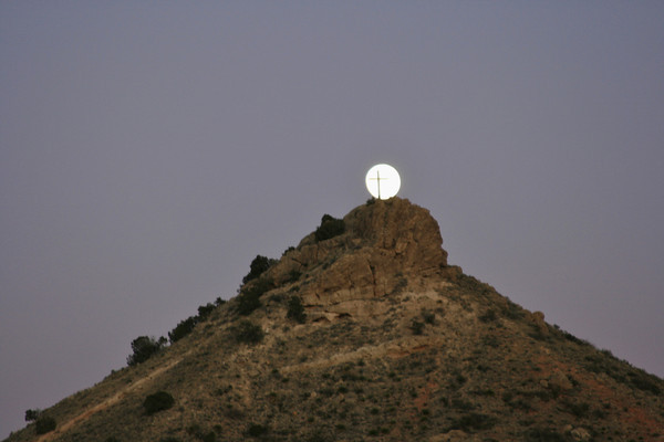 Moon rising and resting atop Round mountain, Mescalero, NM