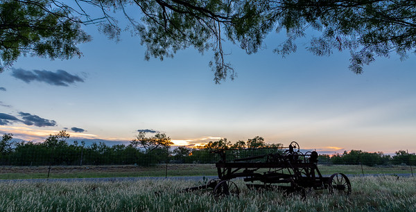 Antique Road Grader foreground as the sun sets