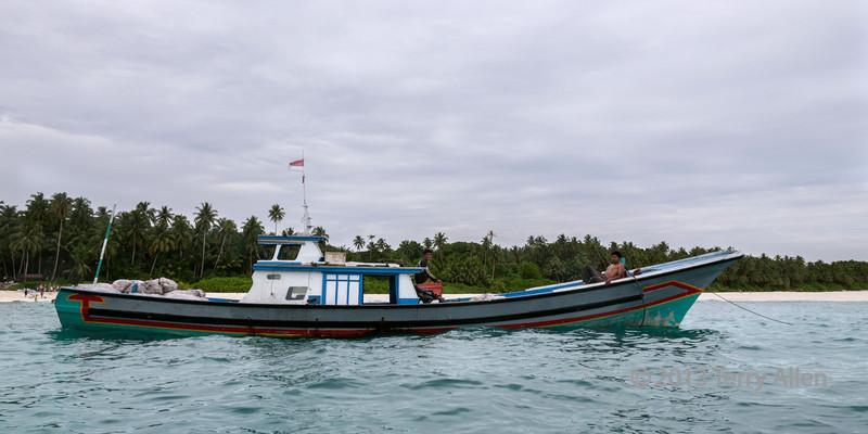Copa boat waiting to load more sacs of coconut hulls, Simeulu Island, Sumatra