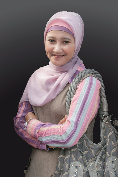 Portrait of a young Acehnese woman, Banda Aceh, Sumatra<br /> <br /> This pretty woman was surrounded by a crowd of people who were very close to her.  The photo was very busy and not pleasing, so I selected her in photoshop and applied a gradient to the background.