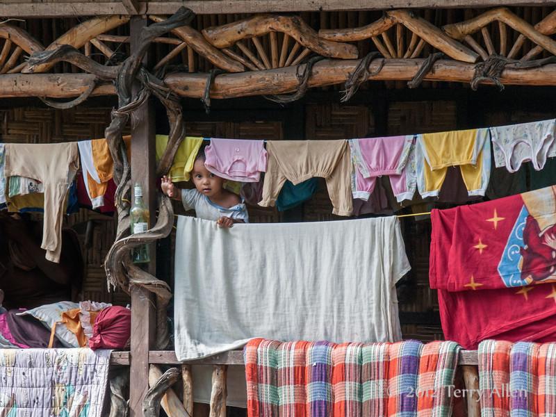 Baby-peeking-out-from-behind-laundry,-traditional-Sumatran-house,-North-Sumatra
