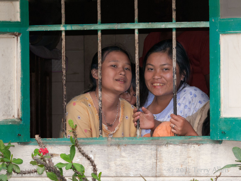 Batak-girls-in-the-window,-Lingga-Brastagi,-North-Sumatra<br /> Note the small pair of eyes peeking from between the two girls